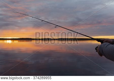 Fishing On The Lake At The Sunset. Hands Of Fisherman With Fishing Rod. Macro Shot. Fishing Rod And