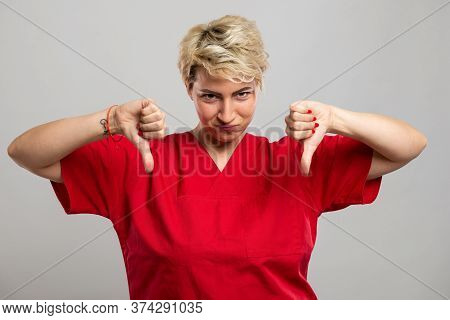 Portrait Of Young Attractive Female Nurse Showing Double Dislike Gesture