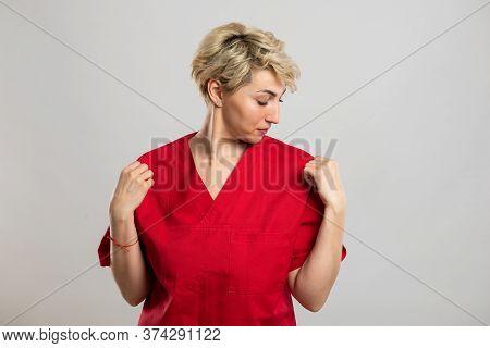 Portrait Of Young Attractive Female Nurse Arranging Shirt