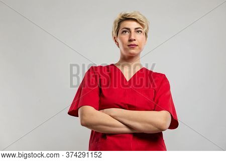 Low Angle Of Attractive Female Nurse Standing With Arms Crossed