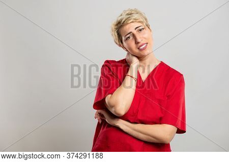Portrait Of Young Attractive Female Nurse Holding Back Neck