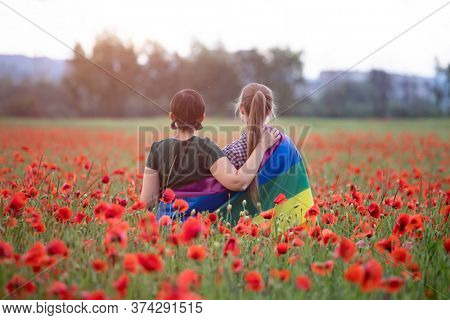 Lesbian couple hugging, holding a Gay Rainbow Flag in beautiful poppy field. Bisexual,gay, lesbian, transsexual symbol. Happiness, freedom and love concept for same sex couples