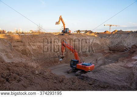 Digging The Pit Foundation A Hole With Excavator. Earthwork In Excavation And Backfilling Of Soil Up