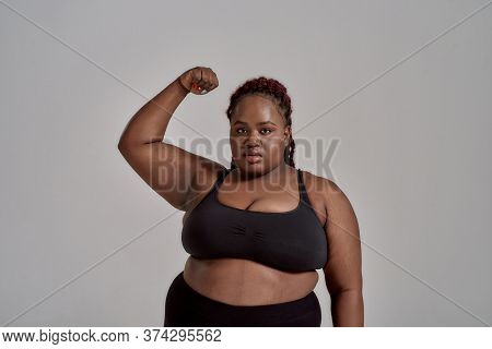 Plump, Plus Size African American Woman In Sportswear Looking At Camera, Showing Strong Arm In Studi