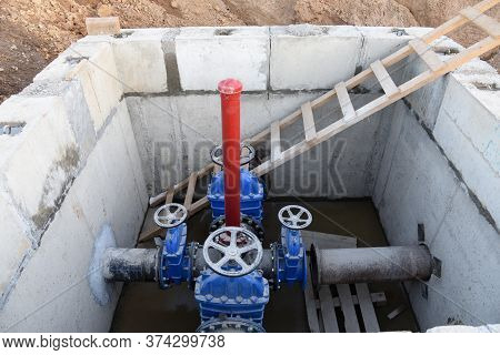 Gate Valves In Valve Pit Of The Underground Piping Networks. Laying Water System Pipeline At Constru