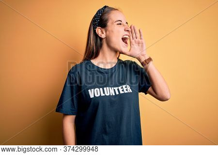 Young beautiful woman wearing volunteer t-shirt doing volunteering over yellow background shouting and screaming loud to side with hand on mouth. Communication concept.