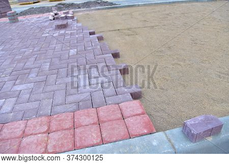 Laying Paving Slabs And Borders At Construction Site. Process Of Installing Paving Bricks In The Tow