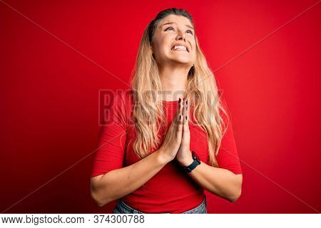Young beautiful blonde woman wearing casual t-shirt standing over isolated red background begging and praying with hands together with hope expression on face very emotional and worried. Begging.