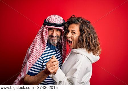 Middle age beautiful couple wearing arab headscarf and sweatshirt smiling happy and confident. Standing with smile on face hugging over isolated red background