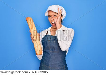 Young beautiful blonde baker woman with blue eyes holding loaf of homemade fresh bread with happy face smiling doing ok sign with hand on eye looking through fingers