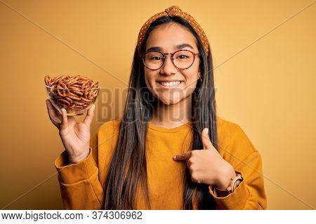 Young beautiful asian woman holding bowl with german baked pretzels over yellow background with surprise face pointing finger to himself