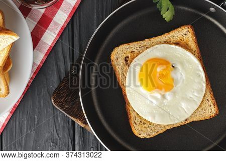 Fried Egg In Frying Pan With Sliced Bread On Wooden Table