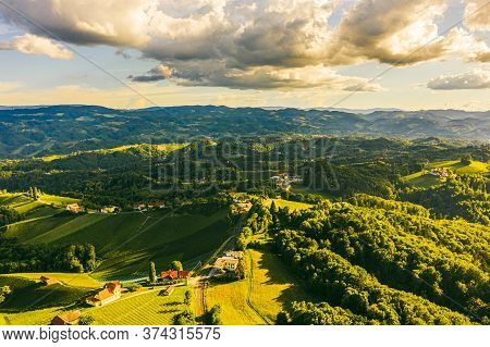 Aerial View Of Green Hills And Vineyards With Mountains In Background. Austria Vineyards Landscape.