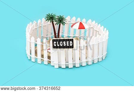 Fenced Miniature Toy Island With Palm Trees, Sun Umbrella And A Sign Saying Closed On Light Blue Bac