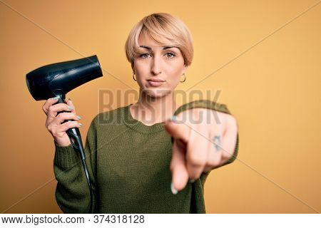 Young blonde woman with short hair drying her hair using hairdryer over yellow background pointing with finger to the camera and to you, hand sign, positive and confident gesture from the front