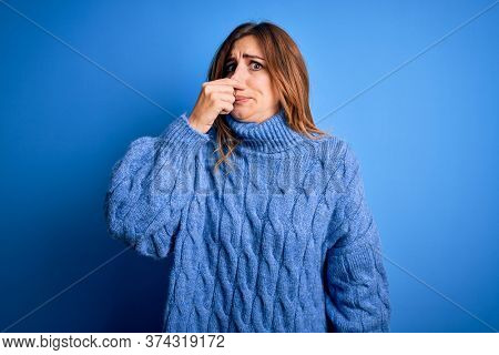 Young beautiful brunette woman wearing casual turtleneck sweater over blue background smelling something stinky and disgusting, intolerable smell, holding breath with fingers on nose. Bad smell