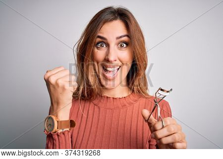 Young beautiful brunette woman using eyelash curler over isolated white background screaming proud and celebrating victory and success very excited, cheering emotion