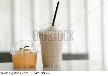 Close Up Glass Of Ice Americano Coffee And Orange Cake On Wood Table, Selective Focus