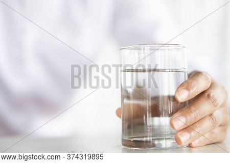 Close Up Woman Hand Holding A Glass Of Pure Water For Dink On The Table, Health Care Concept