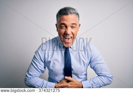 Middle age handsome grey-haired business man wearing elegant shirt and tie smiling and laughing hard out loud because funny crazy joke with hands on body.