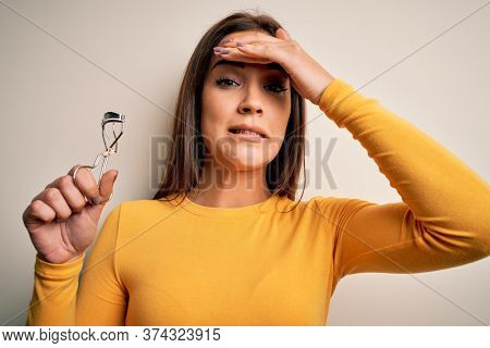 Young beautiful brunette woman holding eyelash curler over isolated white background stressed with hand on head, shocked with shame and surprise face, angry and frustrated. Fear and upset for mistake.