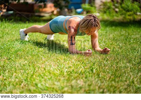 Exercise Plank, Handstand. Blonde Girl With Tattoos Plays Sports In The Garden. Recovery And Fitness