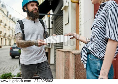 Bearded Delivery Man In Helmet With Thermo Backpack Giving Away Order, Envelope To A Female Customer
