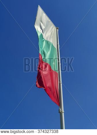 Bulgarian Flag Waving On Blue Sky Background. The Location Is Obzor, Bulgaria. Flag Of Bulgaria Agai