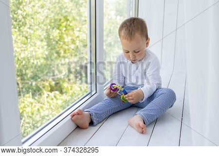 A Small Boy 2 Years Old Is Standing At The Window And Waiting For Mom And Dad