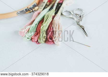 Multi-colored Cotton Floss Thread For Cross-stitch, A Needle, Scissors And A Wooden Hoop On A White