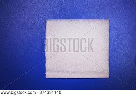 White Square Bar Napkin Isolated On Blue Background . Blank Paper Napkin Isolated On Blue Background