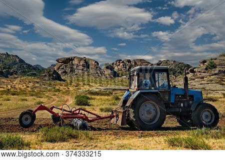 Bayanaul. Kazakhstan. July 31, 2019. A Tractor With A Plow Plows A Strip Of Land Around A Mountain N