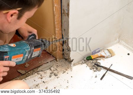 Working With A Hammer To Expand The Doorway