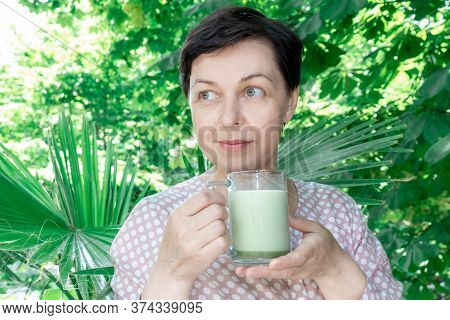 Middle Aged Woman Hold Glass Cup Of Green Matcha Latte Coffee Or Tea On The Tropical Background. Con