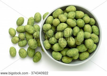 Wasabi Coated Peanuts In A White Ceramic Bowl Next To A Pile Of Wasabi Peanuts Isolated On White. To