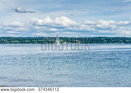 A Sailboat On The Puget Sound With Billowing Clouds Above.