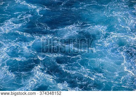 Seething Ice Waves Of The Northern Ocean. Translucent Blue-turquoise Water With Hats Of Sea Foam Bac