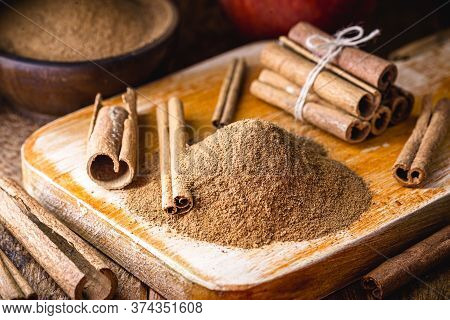 Powdered And Stick Cinnamon On A Rustic Wooden Table. Cinnamomum, Used In Both Sweet And Savory Food