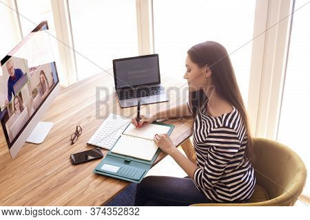 Back View Of Woman Sitting Behind Her Computer And Having Discussion And Online Meeting In Video Cal