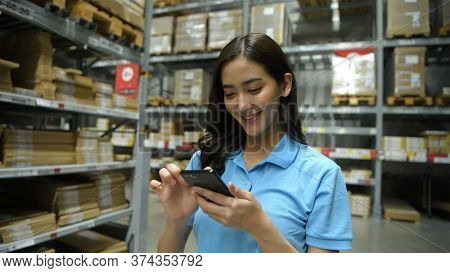 Business Concepts. An Asian Woman Is Checking Products In A Warehouse With An Application From A Mob