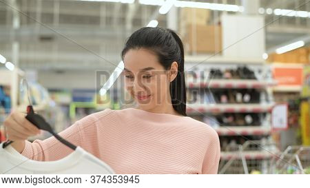 Shopping Concepts. An Asian Woman Is Buying Clothes In The Mall. 4k Resolution.