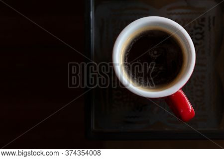 Mug Of Hot Americano Black Coffee On The Top Of The Glass Table With Morning Light At The Coffee Sho