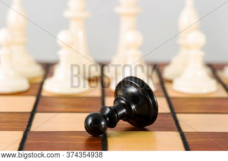 Close-up Of A Black Pawn Lying On A Chessboard And Surrounded By White Pieces. Other Chess Pieces In