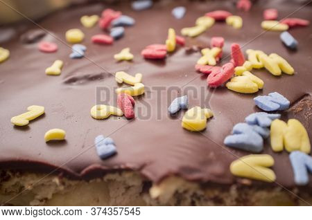 Homemade Chocolate Cake Covered With Glimmer Sugar Letters. Closeup