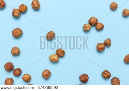 Creative Food Layout. Hazelnuts On Blue Background Top View Copy Space. Concept Of Food, Healthy Nut