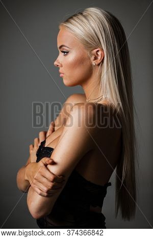 Portrait of blond young woman with beautiful makeup and hairstyle in a black lace dress stands on gray background. Fashion model poses in elegant clothes in studio.