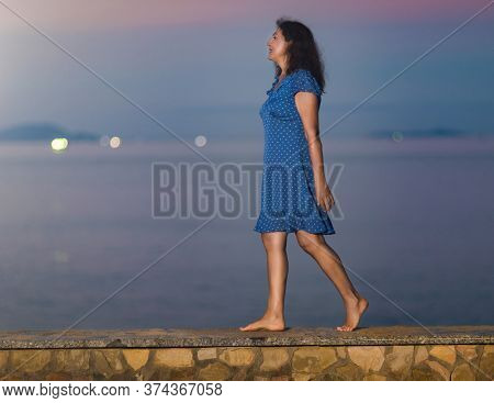 Outdoor portrait of a beautiful smiling senior woman sitting near the sea at sunset
