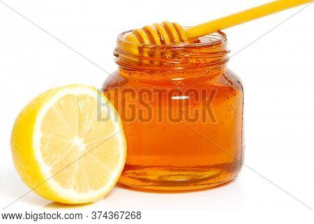bee honey in a glass jar, honey dipper and lemon