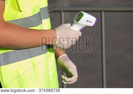 Man In Rubber Gloves And A Uniform Checks The Temperature With A Thermal Imager