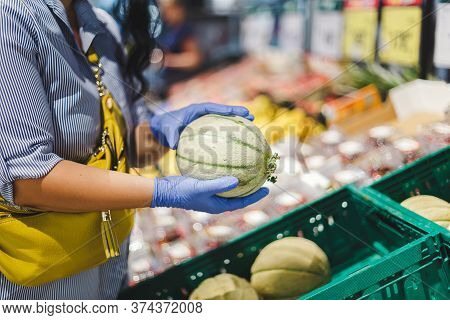 Woman In Protective Gloves Buys Melon In A Supermarket During The Coronavirus Epidemic. Selective Fo